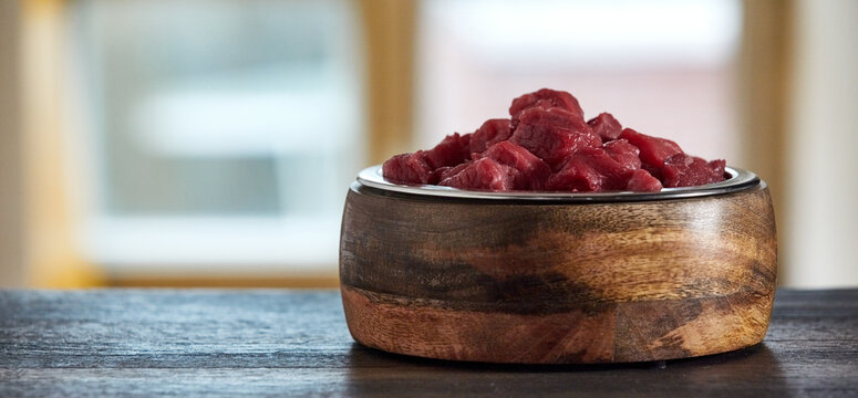 Bowl with raw beef on table