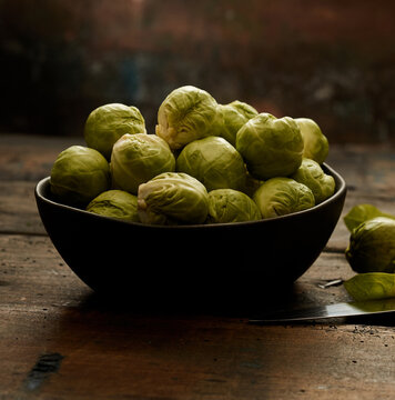 Bowl of organic Brussels sprouts on lumber table
