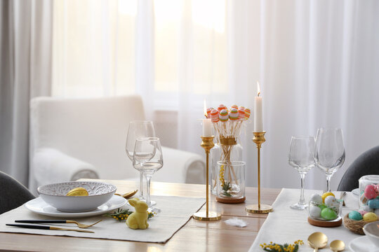 Beautiful Easter table setting with burning candles and floral decor indoors