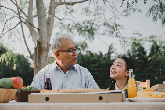 Grandfather and granddaughter having pizza in garden at home. Retirement age lifestyle with family on summer holiday.