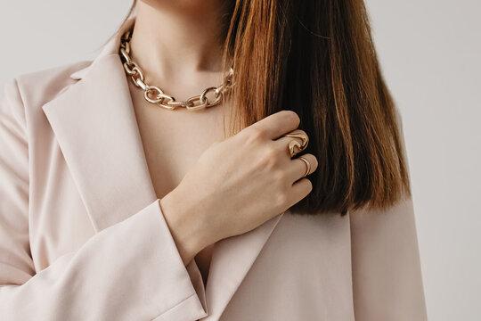 Woman in light beige jacket wearing golden chain necklace.