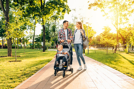 family, dad mom are walking with a little toddler in a stroller in the park