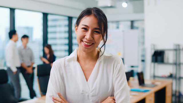 Portrait of successful beautiful executive businesswoman smart casual wear looking at camera and smile, arms crossed in modern office workplace. Young Asia lady standing in contemporary meeting room.
