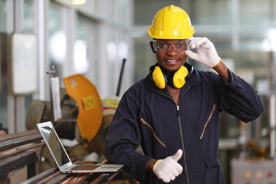 Portrait of African American mechanic engineer worker wearing safety equipment beside the sawing machine in manufacturing factory