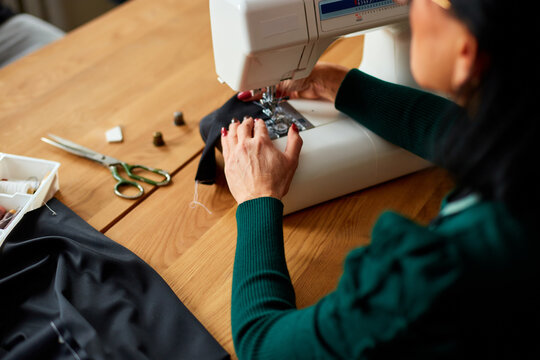 Step by step, 50-yers old woman sews clothes on sewing machine