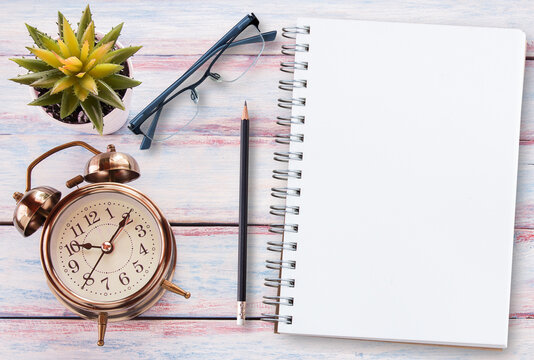 Retro alarm clock,blank notebook,glasses and flower on a wooden table. Photo in retro color image style.