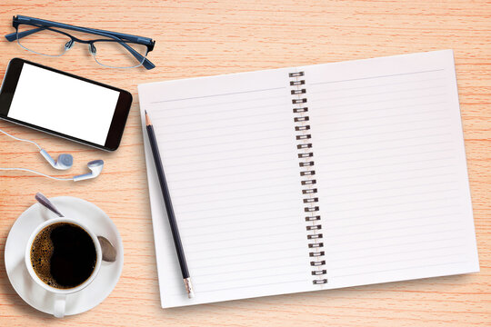 Smart phone,blank notebook,glasses and earphone with cup of coffee on old wooden background
