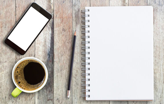 Smart phone,blank notebook,pencil and cup of coffee on wood table.