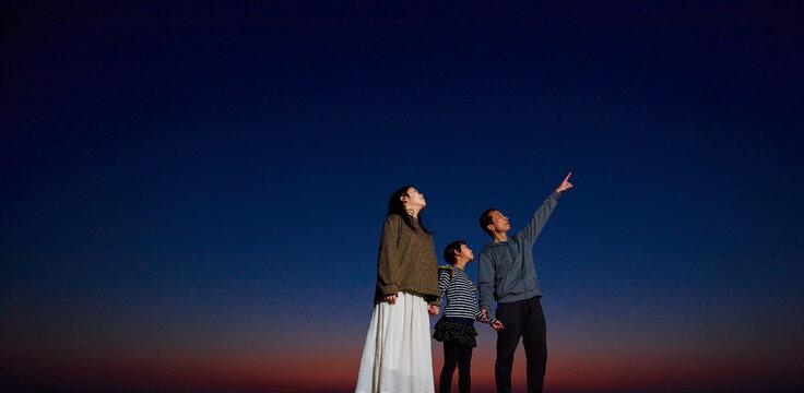 綺麗な夕焼けの空と星を見ている親子の姿