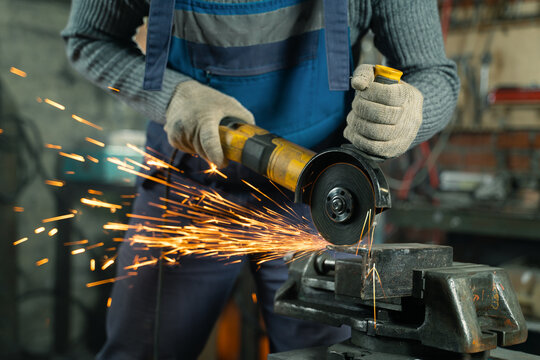 Locksmith in special clothes and goggles works in production. Metal processing with angle grinder. Sparks in metalworking