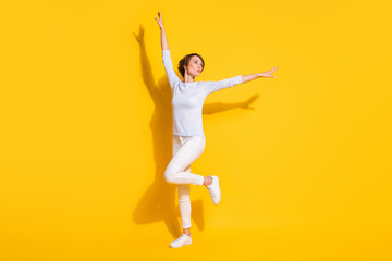 Full length photo of sweet funky young lady dressed white shirt dancing isolated yellow color background