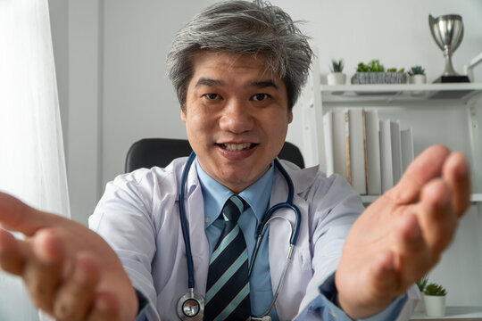 Asian doctor is online visiting with a patient on the internet application and make a note of the symptoms and explain how to treat the initial disease