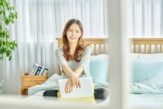 동양인 한국인 여성 모델 침대 위에서 노트북을 보며 스트레칭