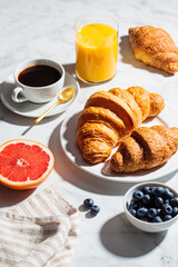 Breakfast concept. Fresh croissants with berries, cup of coffee and glass of orange juice on white marble background.