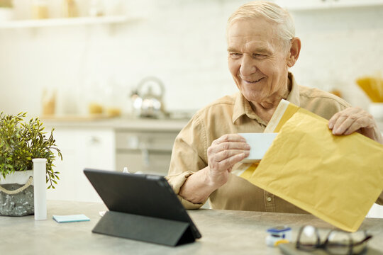 Contented aged man with parcel looking at tablet screen