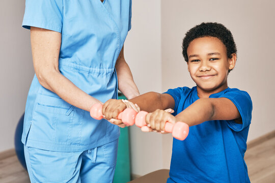 Physiotherapist working with child patient in a rehab clinic. Boy raises dumbbells, strengthening arm muscles and developing joints
