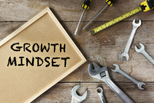 Growth mindset word on frame with tools supplies on wooden background. Success effort with freedom concept and challenge idea