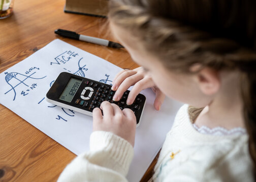 Cute pretty young girl doing complex maths writing calculations genius child at home school using scientific calculator to do advanced arithmetic