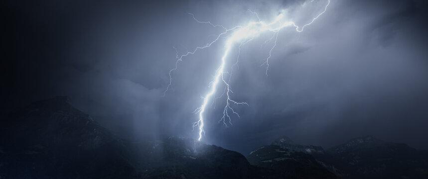Lightning over mountains and lake. Switzerland.