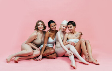 Group of multiethnic women with different kind of skin posing together in studio. Concept about...