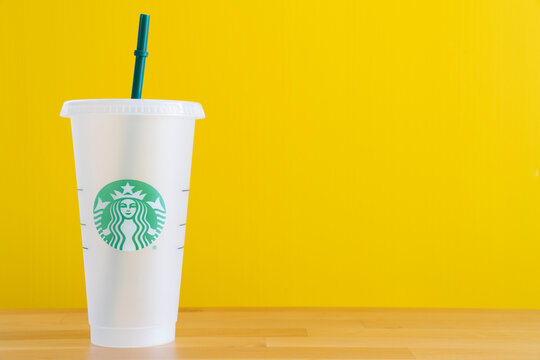 Bangkok, Thailand -JAN 24, 2021: Close up a cup of Starbuck coffee and straw on the table with yellow background