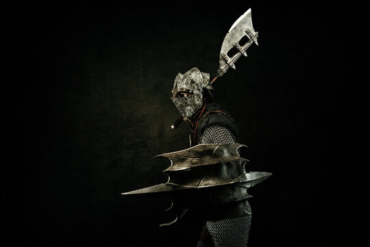 Medieval fighter in armor, in profile, carrying a shield and an ax on his shoulder, in attack position