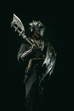 Medieval fighter in armor, carrying a shield and an ax on his shoulder