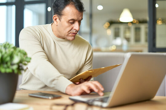 Busy latin middle aged businessman holding document envelope while working using laptop at home
