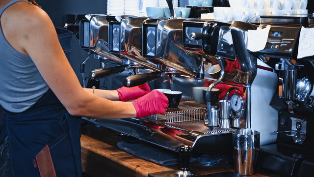 partial view of barista holding cups near modern coffee machine in coffee shop