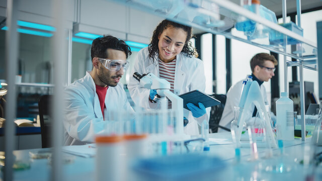 Modern Medical Research Laboratory: Portrait of Latin and Black Young Scientists Using Microscope, Digital Tablet, Doing Sample Analysis, Talking. Diverse Team of Specialists work in Advanced Lab