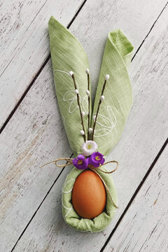 Bunny Ears from green napkin with egg on natural wooden background to Celebrate Easter