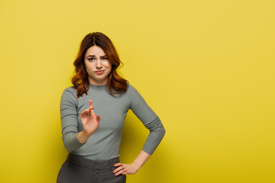 displeased woman standing with hand on hip and pointing with finger while showing no sign on yellow