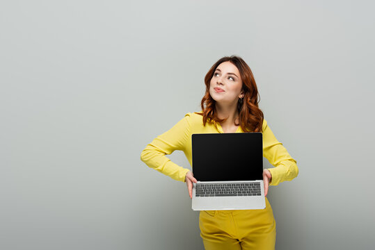 smiling woman looking away while holding laptop with blank screen on grey