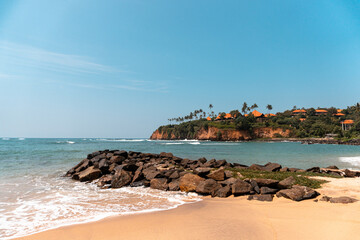 Krajobraz wybrzeża nad oceanem, klif, kamienie oraz plaża.