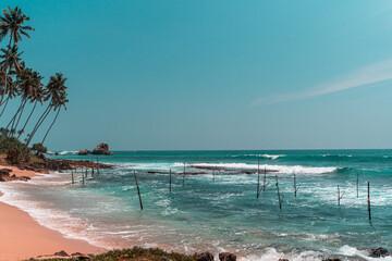 Tropikalna plaża z palmami, niebieski ocean z falami oraz kije rybackie.