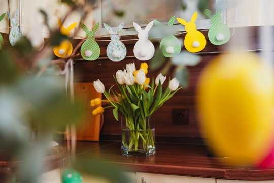 Decorated for Easter kitchen. Garlands of hare figures and live tulips in a vase on the table.