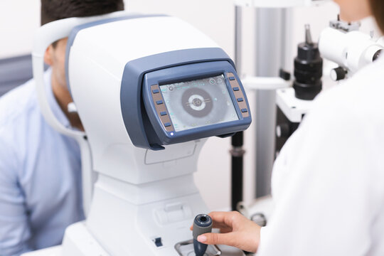 Optometrist checking patients vision at the modern clinic