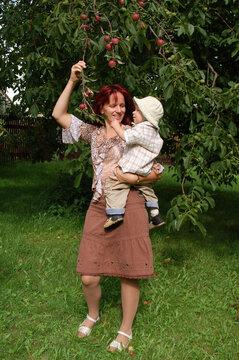 Frau mit Kind auf dem Arm am Apfelbaum