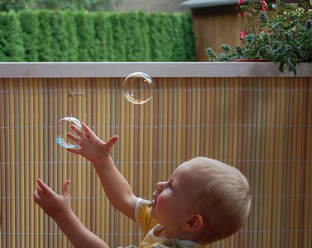 Kind beim Seifenblasen fangen im Sommer