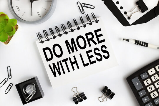 do more with less. text on white notepad paper on light background near calculator, plant, table clock.