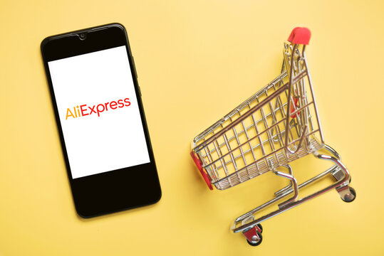 Aliexpress logo on black screen of smartphone with shopping cart