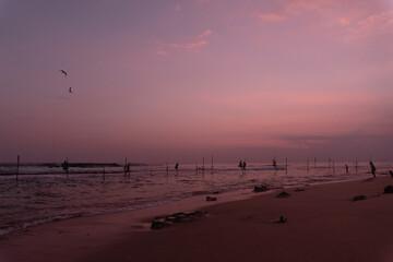 Tradycyjni rybacy wędkarze podczas połowy na palach w oceanie, na tle zachodzącego słońca.
