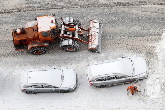 Worker and snow plow machine removing the snow on the parking lot, top view. Snowfall in winter city, cars got stuck