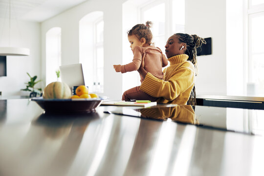 Young mom looking after her girl while working from home.