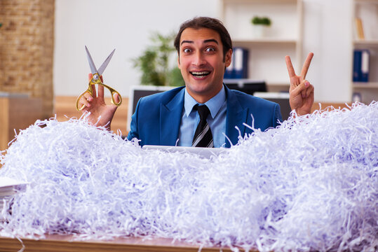 Young male employee and a lot of cut papers in the office