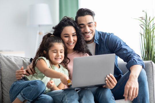 Online Shopping. Happy Arabic Family Using Laptop And Credit Card At Home