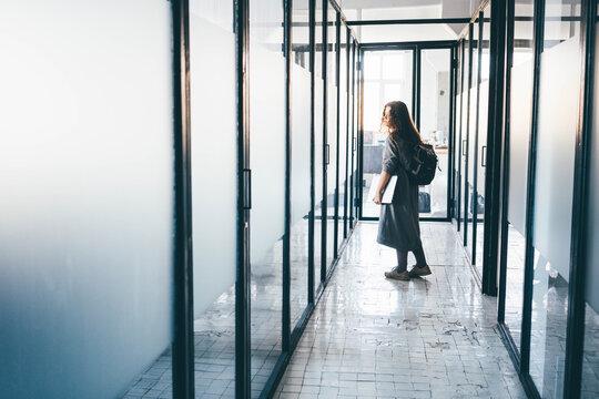 Business woman leaving office.Businesswoman walking in office corridor.