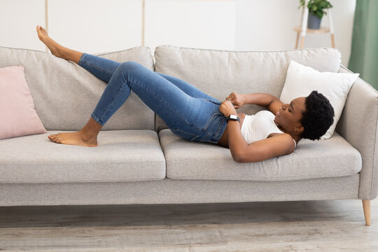 Black Woman Struggling Zipping Small Jeans Lying On Sofa Indoors