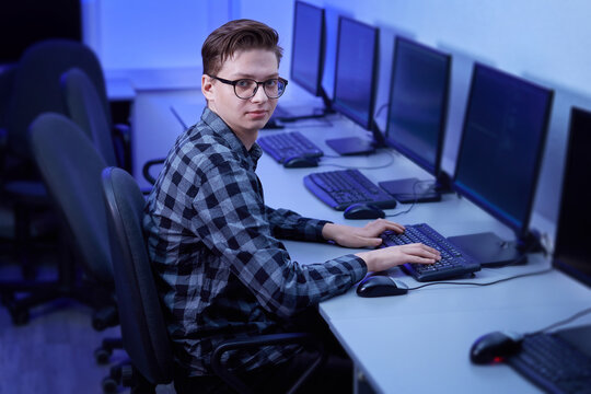 Vertical photo of a young man wearing glasses for vision. He looks at the camera. The work of a programmer in the office.