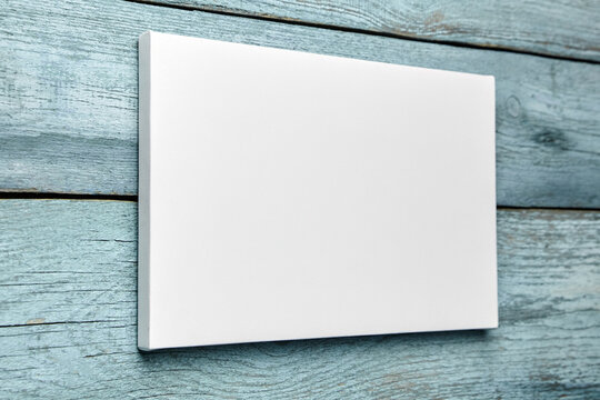 Canvas hanging on light blue wooden wall, white canvas print mockup